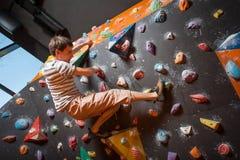 Escalador masculino fuerte en la pared que sube del canto rodado interior Imagenes de archivo