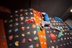 Escalador masculino fuerte en la pared que sube del canto rodado interior Fotos de archivo