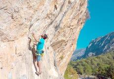 Escalador masculino maduro que hace movimiento en roca vertical Imágenes de archivo libres de regalías