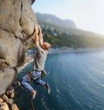 Escalador masculino que sube el canto rodado grande en naturaleza con la cuerda Foto de archivo