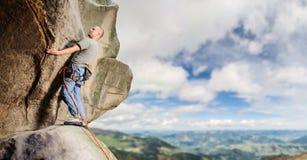Escalador masculino que sube el canto rodado grande en naturaleza con la cuerda Foto de archivo libre de regalías
