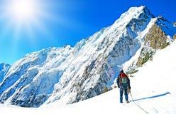 Escalador que alcanza la cumbre de la montaña Fotografía de archivo