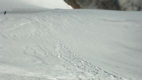 Escalador que se levanta por la cuesta de montaña nevosa subida en el soporte de Kazbek en el día ventoso soleado almacen de metraje de vídeo