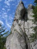 Escalador que sube una roca Foto de archivo libre de regalías