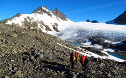 Escaladores de la gente, subiendo a la cumbre, a los picos de montaña rocosa y al glaciar en Noruega Foto de archivo