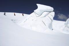 Escaladores de montaña que caminan más allá de la formación de hielo Foto de archivo libre de regalías