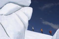 Escaladores de montaña que caminan más allá de la formación de hielo Imagen de archivo