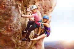 Escaladores de roca que alcanzan la cumbre de una montaña Imágenes de archivo libres de regalías