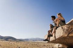 Escaladores de roca que se sientan en roca contra el cielo azul Fotografía de archivo
