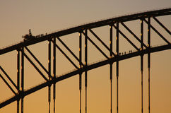 Escaladores en el puente de puerto de Sydney en la puesta del sol Fotos de archivo