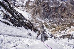 Escaladores en la ruta, el hombre en el nea derecho de la chaqueta brillante Fotos de archivo