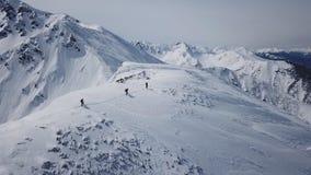 Escaladores que caminan encima de subida épica de la cordillera del vuelo aéreo de la expedición de la montaña al invierno máximo metrajes