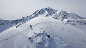Escaladores que caminan encima de subida ?pica de la cordillera del vuelo a?reo de la expedici?n de la monta?a al invierno m?ximo metrajes