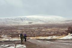 Escaladores que caminan a lo largo del camino en valle en Escocia fotos de archivo