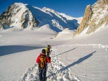 Escaladores que cruzan el glaciar del du Midi de la cuesta en la nieve fresca que hace t Imagen de archivo libre de regalías