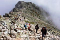 Escaladores que suben al pico de Krivan Imágenes de archivo libres de regalías