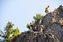 Escaladores que suben en roca Imagenes de archivo
