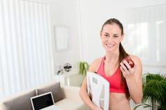Escalas alegres de la tenencia de la mujer joven y consumición de programa de la pérdida de peso de la fruta Fotografía de archivo libre de regalías