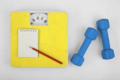Escalas, caderno com lápis e um dumbbell. fotos de stock