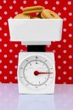 Escalas da cozinha com conceito da dieta dos bolinhos fotos de stock