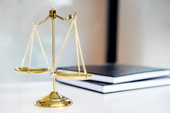 Escalas da lei ou livros dourados do peso e dos legals na tabela Símbolo de Imagens de Stock Royalty Free
