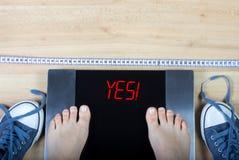 Escalas de Digitas com pés fêmeas neles e sinal cercado por gymshoes e pela fita de medição imagem de stock