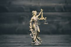 Escalas de justiça, Justitia, senhora Justice em um fundo de madeira preto imagem de stock