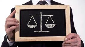 Escalas de la justicia dibujadas en la pizarra en las manos del abogado, pros de la decisión - y - contra stock de ilustración
