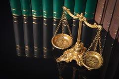 Escalas de oro de la justicia delante de los libros de ley Imágenes de archivo libres de regalías