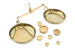 Escalas de oro lanzadas del balance con los pesos Fotos de archivo libres de regalías