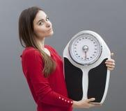 20 escalas elegantes felices de la tenencia de la muchacha para comprobar pérdida de peso Imágenes de archivo libres de regalías