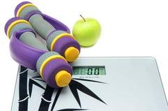 Escalas, manzana y pesas de gimnasia Foto de archivo libre de regalías