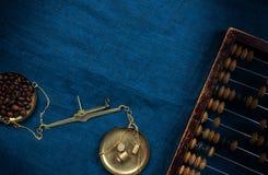 Escalas velhas do manual com as contagens pequenas dos pesos e dos feijões de café em um pano azul fotografia de stock royalty free