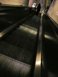 Escalator. Photo of a woman on an escalator descending to a subway platform royalty free stock photo