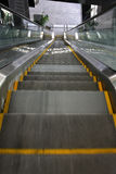 Escalator. Looking down a moving escalator with glass handrail Royalty Free Stock Photography