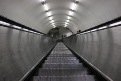 Escalator. Stainless steel escalator leading down to a metro station Royalty Free Stock Images