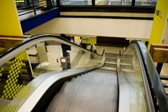 Escalator at an airport. An escalator at an airport, one person at the foot of it, yellow banner, the stairs blurred Royalty Free Stock Photography