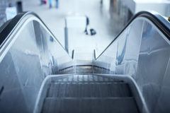Escalator in airport. Tilt-shift lens used to accent the stairs and sublime blue cast applied for more business effect Stock Image