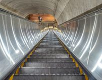 Escalator descending into dark tunnel of subway station. An escalator descending into dark tunnel of underground subway station Stock Photography