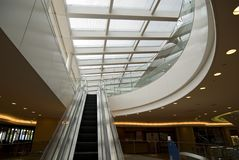 Escalator hall interior. Modern building interior with moving escalator and glass roof Stock Photos