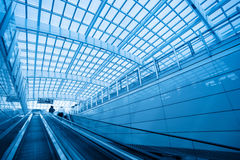 The escalator leading to the modern airport. Escalator in modern interior airport Royalty Free Stock Image
