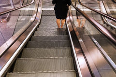 Escalator with legs of a woman