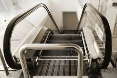 Escalator with lines outlining every steps for marking boundary of safety area. Installed bollard on top of escalator to prevent and stop baggage trolleys Stock Image