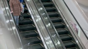 Escalator in the mall, it works. People ride it, woman and her son.  stock video