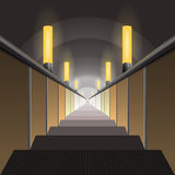 Escalator in the metro. Descend under lighting fixtures yellow Royalty Free Stock Photography