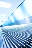 Escalator mobile bleu dans le hall de bureau Photographie stock libre de droits