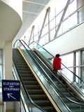 Escalator modern building. Woman in red jacket going up escalator in a modern building Royalty Free Stock Photography