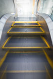 Escalator is moving to the next level. Blurry moving escalator before reaching the next floor with soft light in distance Royalty Free Stock Photography