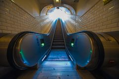 Escalator perspective to the exit tunnel Metro Paris royalty free stock photography