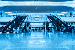 Escalator in railway station hall. Escalator in modern railway station hall with passengers motion blur Stock Image